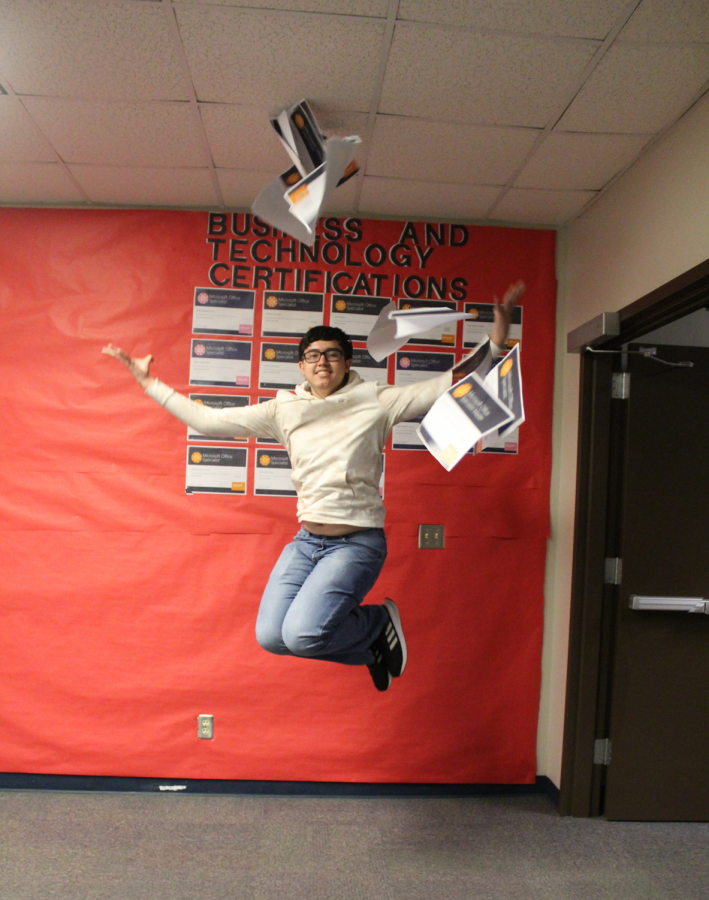 Richard Davis jumps for joy while tossing his certificates in the air.