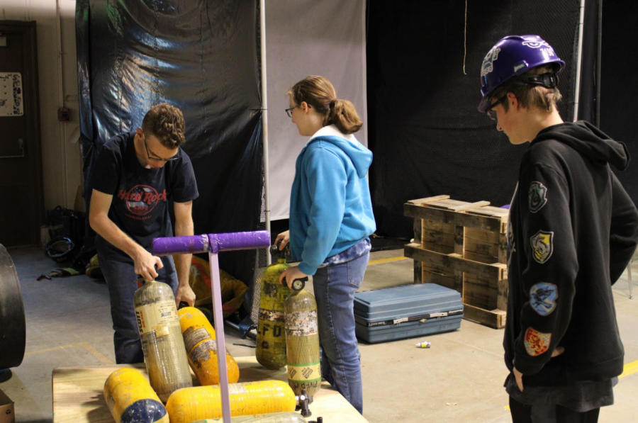 """Safety Mania Max Yoder (right) at the robotics shop on Tuesday. Max Yoder, the safety Captain is supervising the moving of gas canisters. When asked how How important safety was to FIRST he said, """"Safety is one of the most important things in FIRST Robotics."""""""