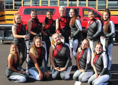 "The Spirit of Twin Lakes Color Guard in their 2019 uniforms. The show's title is ""Off the Rails"". The team includes 12 members."