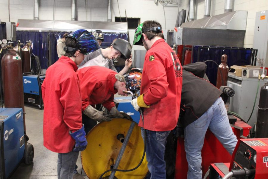 Ms. R's welding students  work on putting the community park's merry go round back together.