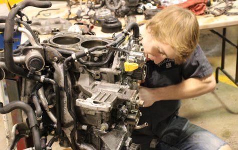 Brayden Plunkett works on an engine in Automotive class.