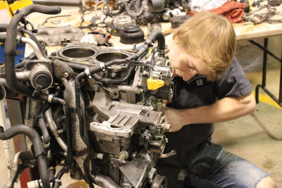 Brayden Plunkett works on an engine in Automotive class.