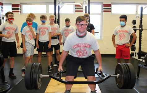 Eric Fisher, freshman, lifting weights in gym class. His classmates are in the background supporting him while trying to lift weights. Eric works hard to get stronger everyday.