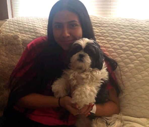 Senior Sheyla Covarrubias is pictured cuddling her dog during the week that Twin Lakes High School holds classes virtually. She is happy to have company while she is at home doing her classwork.