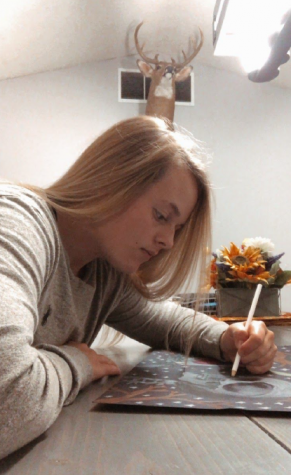 """Online school for the win. Senior Olivia Crawn is working on an art project. """"This art project really helped me stay distracted from the outside world,"""" said Crawn. Mrs. Padlo is having her Drawing II students work on Surrealism."""